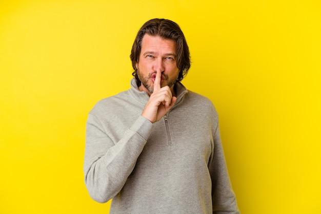 Uomo di mezza età isolato sulla parete gialla mantenendo un segreto o chiedendo silenzio