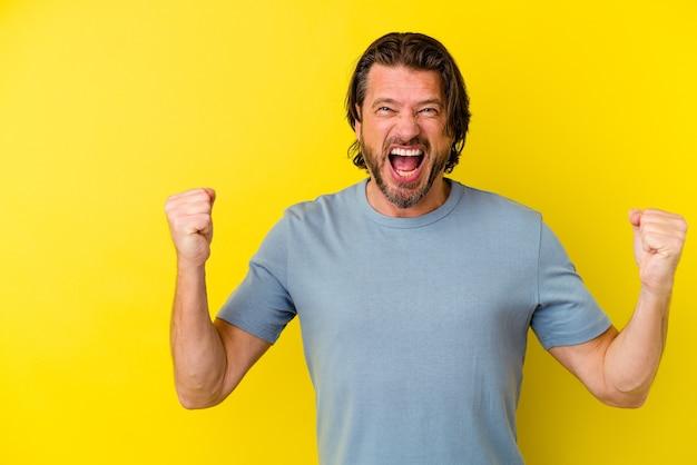 Uomo di mezza età isolato sulla parete gialla che alza il pugno dopo una vittoria, concetto del vincitore