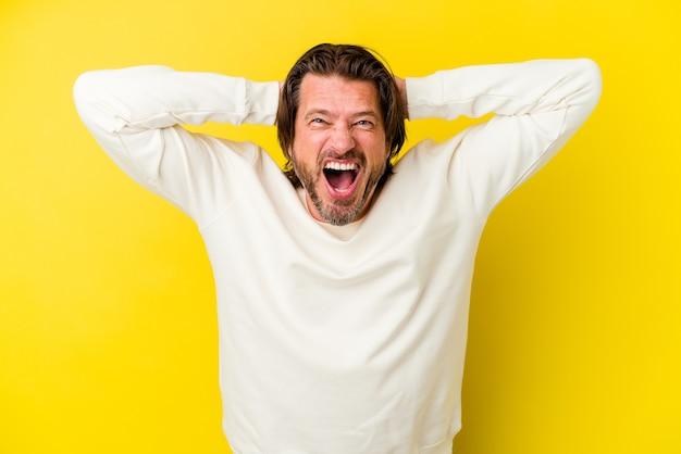 Uomo di mezza età isolato sulla parete gialla che grida di rabbia