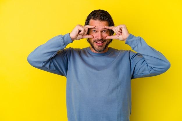 Uomo di mezza età isolato sulla parete gialla che mostra il segno giusto sopra gli occhi