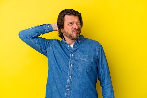 Uomo di mezza età isolato sulla parete gialla che soffre di dolore al collo a causa dello stile di vita sedentario