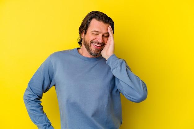 Uomo di mezza età isolato sul muro giallo stanco e molto assonnato tenendo la mano sulla testa