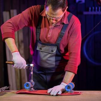 Uomo di mezza età in tuta che fissa lo skateboard in plastica rossa per bambini nel laboratorio di casa con una chiave a bussola. padrone domestico capace e affidabile
