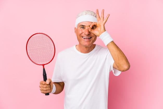 Uomo di mezza età che gioca a badminton isolato eccitato mantenendo il gesto giusto sull'occhio.