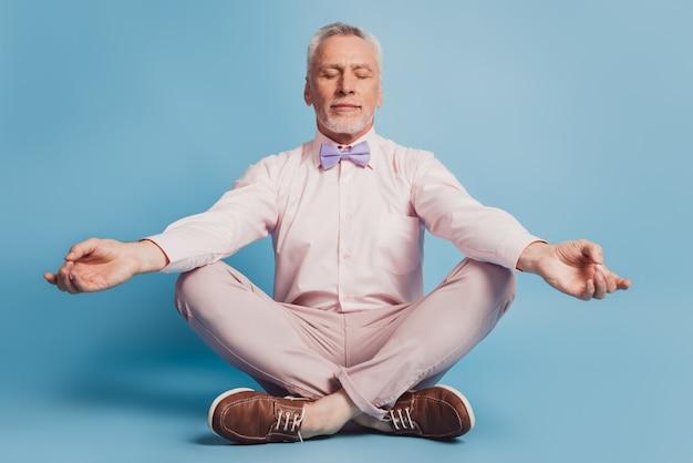 Uomo di mezza età che pratica yoga seduto sul pavimento di colore blu sfondo