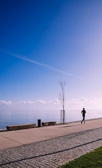 Uomo di mezza età che corre, lavora, fa esercizio sul lungomare. concetto di assistenza sanitaria. concetto di sport