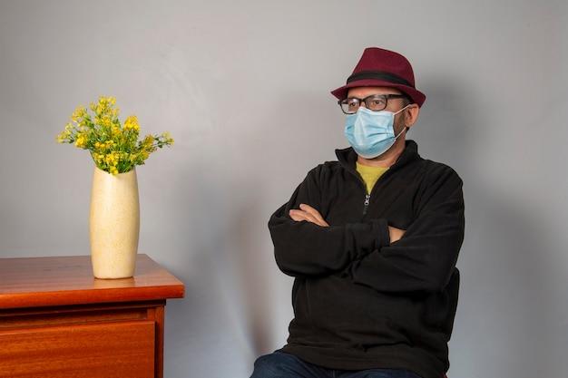 Uomo di mezza età seduto con un cappello e una maschera di protezione pantemica. . .