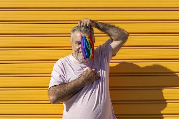 Uomo di mezza età che indossa un cappello, occhiali da sole e una maschera protettiva color arcobaleno. lgtb su sfondo giallo. concetto covid-19