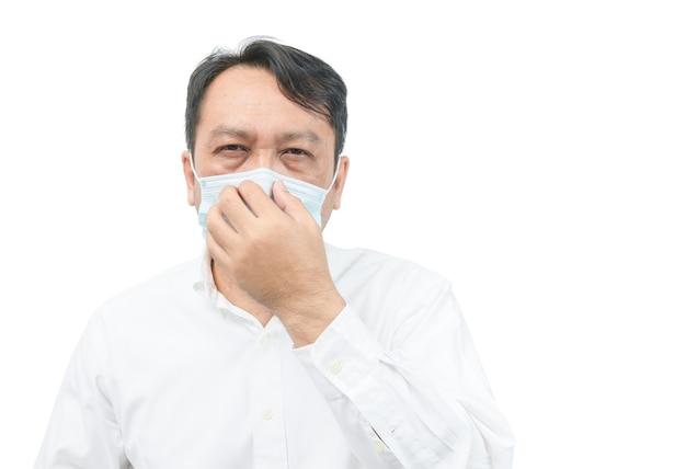 Un uomo di mezza età che indossa una camicia bianca, indossa una maschera e si copre il naso con la mano. proteggere il coronavirus o il covid-19 e il concetto di inquinamento atmosferico