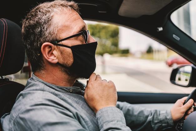 Uomo di mezza età con gli occhiali, con la maschera protettiva sul viso seduto nella sua auto e guidandola durante l'epidemia del coronavirus.