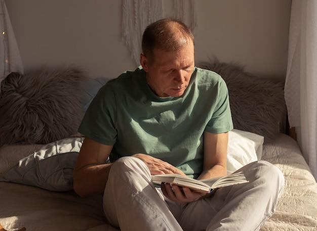 Libro di lettura uomo maturo di mezza età in casa accogliente, luce del giorno.