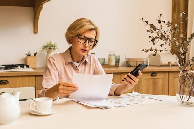 Donna anziana matura di mezza età che tiene una fattura cartacea o una lettera a casa per effettuare pagamenti online sul sito web sul telefono cellulare, calcolare il costo delle tasse finanziarie, rivedere il conto bancario.