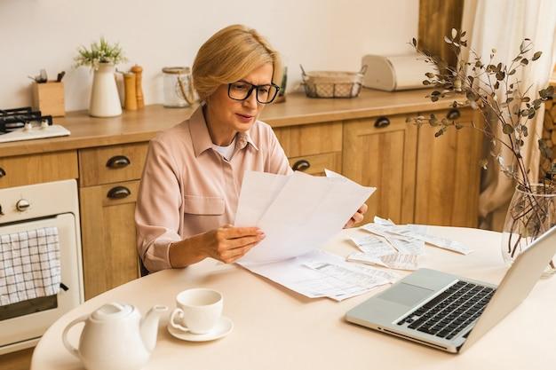 Donna anziana matura di mezza età che tiene una fattura cartacea o una lettera utilizzando il computer portatile a casa per effettuare pagamenti online sul sito web, calcolare il costo delle tasse finanziarie, rivedere il conto bancario.