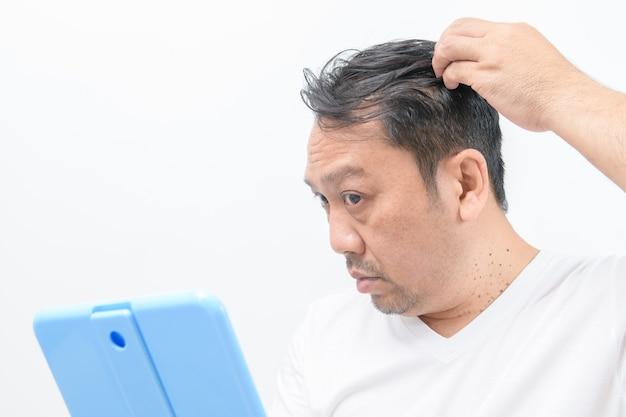 Gli uomini di mezza età si preoccupano della caduta dei capelli o della crescita dei capelli isolati un muro bianco,
