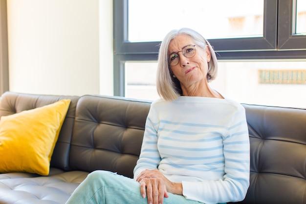 Bella donna di mezza età che si sente confusa e dubbiosa, chiedendosi o cercando di scegliere o prendere una decisione