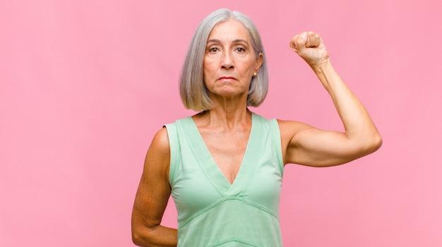 Bella donna di mezza età che si sente inorridita e scioccata, alza le mani sulla testa e si fa prendere dal panico per un errore