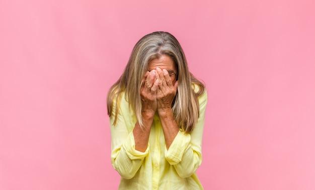 Donna graziosa di mezza età che si sente stressata, ansiosa, stanca e frustrata, tira il collo della camicia, sembra frustrata dal problema