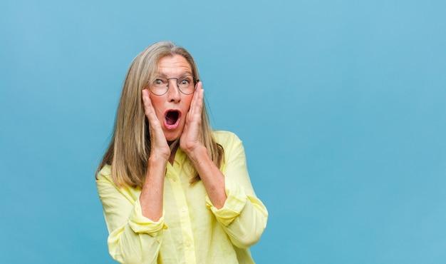 Bella donna di mezza età che si sente terrorizzata, indietreggia e urla in preda all'orrore e al panico, reagendo a un incubo