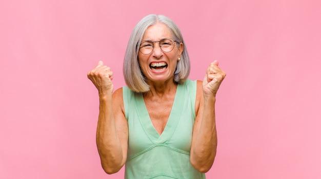 Donna graziosa di mezza età che tiene la guancia e soffre di mal di denti doloroso, sensazione di malessere, infelice e infelice, alla ricerca di un dentista