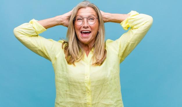 Donna graziosa di mezza età che sembra stressata e frustrata, lavora sotto pressione con un mal di testa e tormentata dai problemi