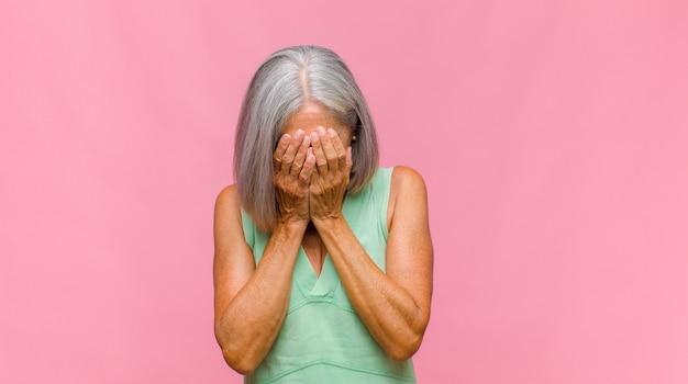 Bella donna di mezza età che sembra stressata, stanca e frustrata, asciugandosi il sudore dalla fronte, sentendosi senza speranza ed esausta