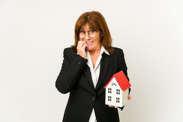 Agente immobiliare di mezza età in possesso di un modello di casa isolato unghie mordaci, nervose e molto ansiose.