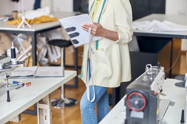 La sarta di mezza età tiene il metro a nastro e i documenti in piedi vicino a tavoli con macchine da cucire