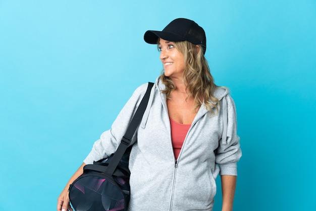 Donna sportiva di mezza età su sfondo isolato guardando lato
