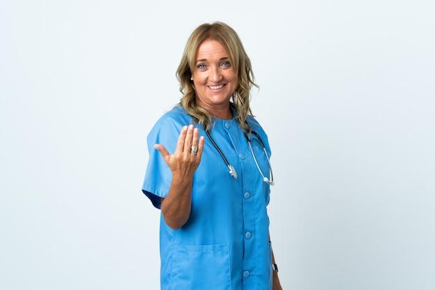 Donna di mezza età chirurgo su sfondo isolato che invita a venire con la mano. felice che tu sia venuto