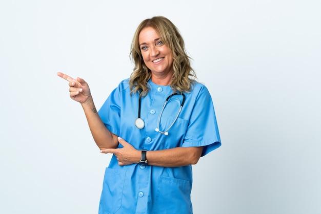 Donna chirurgo di mezza età su sfondo isolato che punta il dito a lato