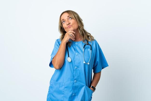Donna di mezza età chirurgo sopra isolato e alzando lo sguardo