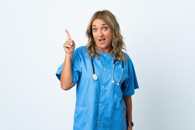 Donna di mezza età chirurgo sopra isolato pensando un'idea che punta il dito verso l'alto