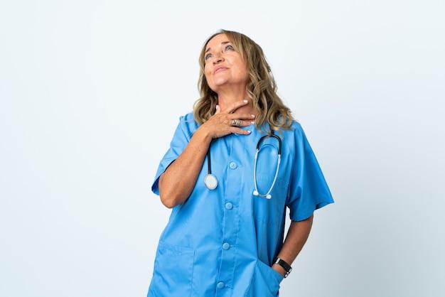 Donna di mezza età del chirurgo sopra la parete isolata che osserva in su mentre sorride