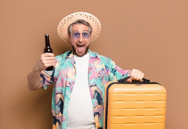 Uomo turistico di mezza età con bottiglia e bagagli