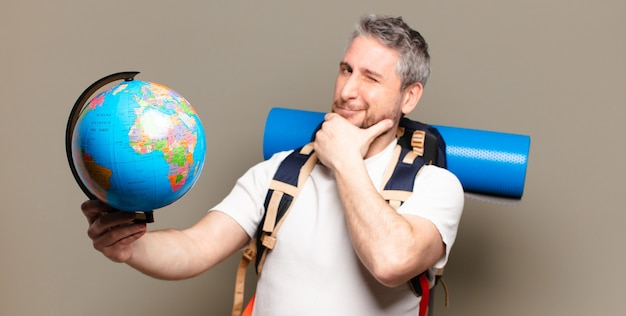 Uomo di mezza età viaggiatore con una mappa del globo del mondo