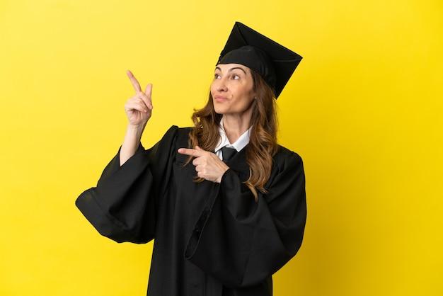 Laureato di mezza età isolato su sfondo giallo che indica con il dito indice una grande idea