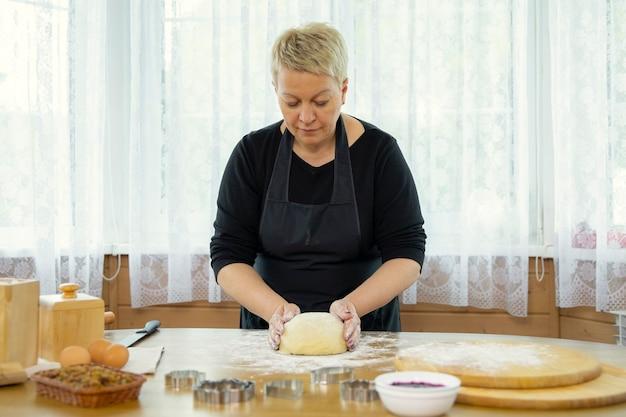 Donna di mezza età in grembiule nero che produce biscotti fatti in casa che impastano la pasta in cucina