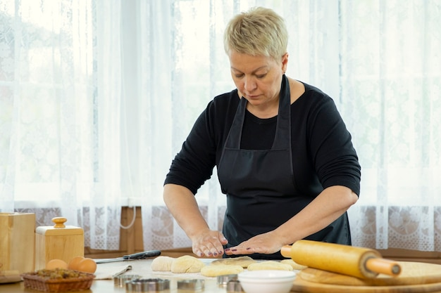 Donna di mezza età in grembiule nero che produce biscotti fatti in casa