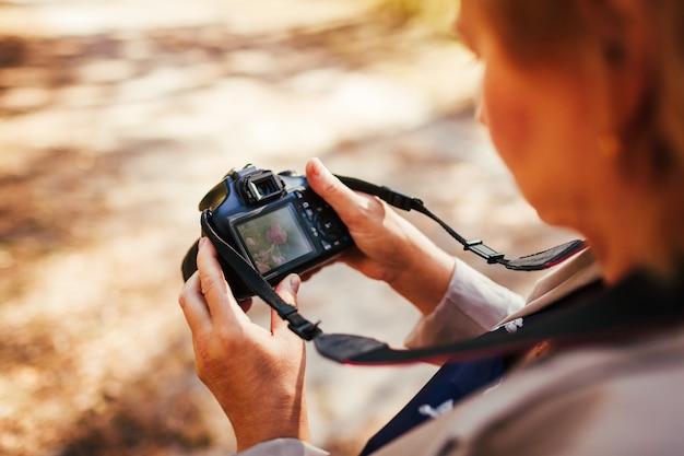 Donna di mezza età che controlla le immagini sulla fotocamera nella foresta autunnale. elegante donna anziana che cammina e si diverte a scattare foto per hobby