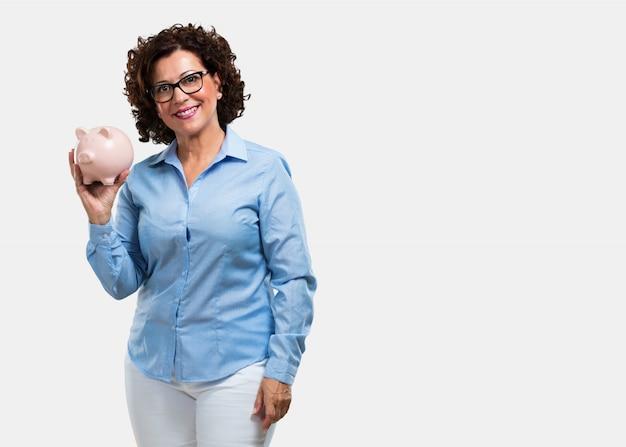 Donna di mezza età fiduciosa e allegra, con in mano una banca di maialini e tranquilla perché i soldi vengono salvati