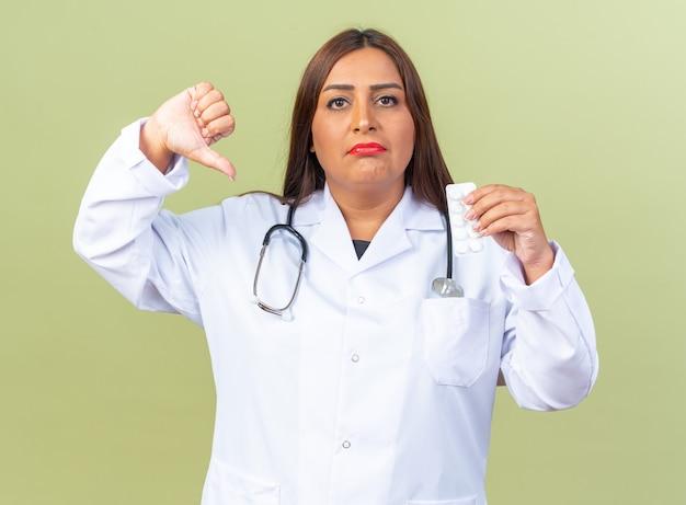 Medico donna di mezza età in camice bianco con stetoscopio che tiene blister con pillole che sembra dispiaciuto che mostra il pollice verso il basso in piedi sul muro verde