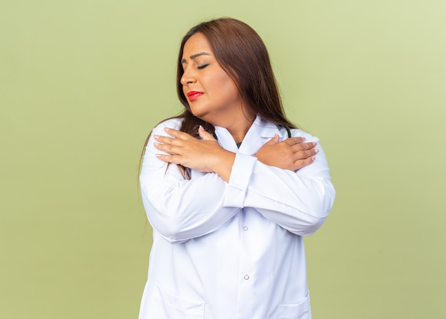 Medico donna di mezza età in camice bianco con stetoscopio che si tiene per mano sul petto con gli occhi chiusi sentendo emozioni positive in piedi sul muro verde