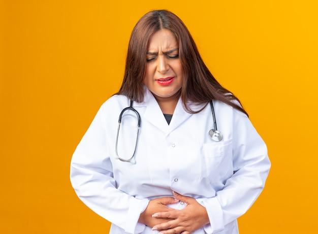 Medico donna di mezza età in camice bianco con lo stetoscopio che tocca la pancia che sembra male sentendo dolore in piedi sul muro arancione
