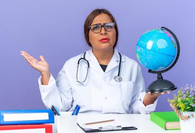 Medico donna di mezza età in camice bianco con stetoscopio con gli occhiali che tiene il globo guardando davanti con il viso serio accigliato con il braccio fuori seduto al tavolo sul muro blu