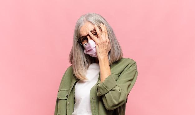 Donna di mezza età che si sente annoiata, frustrata e assonnata dopo un compito noioso, noioso e noioso, tenendo il viso con la mano