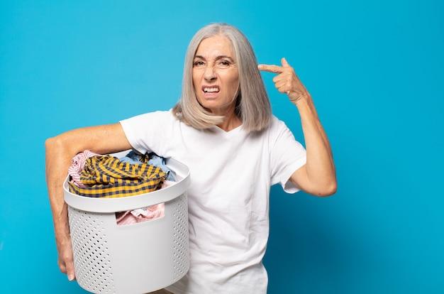 Donna di mezza età che si sente confusa e perplessa, dimostrando che sei pazzo, pazzo o fuori di testa