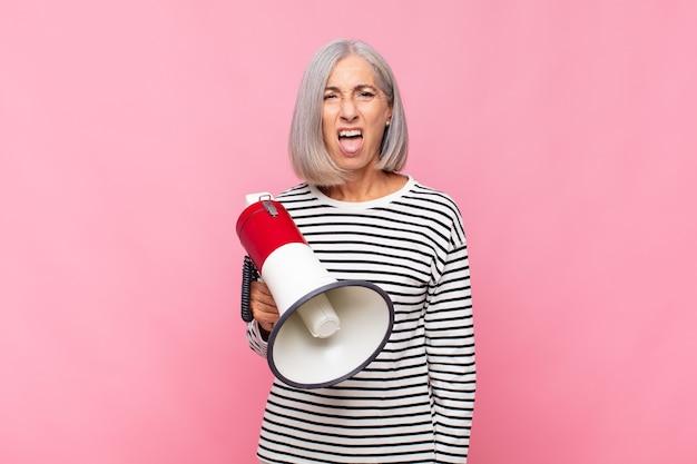 Donna di mezza età che si sente disgustata e irritata, sporge la lingua, non ama qualcosa di brutto e schifoso con un megafono