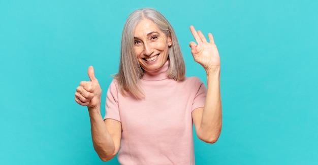 Donna di mezza età che si sente felice, stupita, soddisfatta e sorpresa, che mostra gesti ok e pollice in alto, sorridente