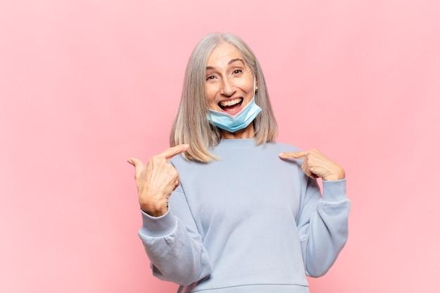 Donna di mezza età che si sente felice, sorpresa e orgogliosa, indicando se stessa con uno sguardo eccitato e stupito