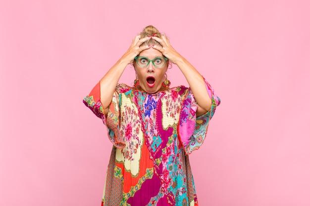 Donna di mezza età che si sente inorridita e scioccata, alza le mani alla testa e si fa prendere dal panico per un errore